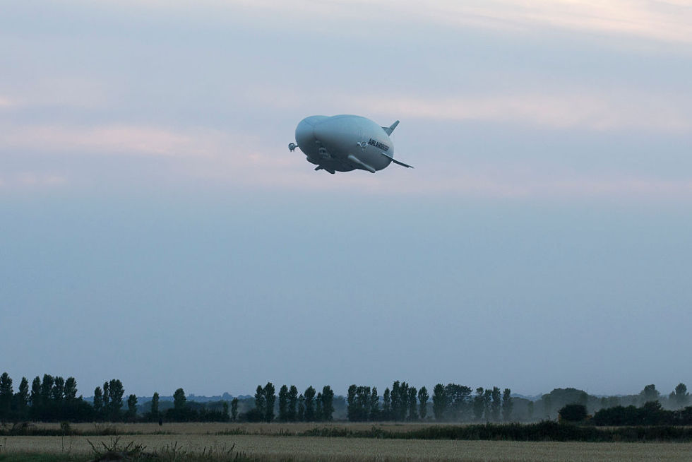 The Hybrid Air Vehicles HAV 304 Airlander 10 hybrid airship is seen in the air on its maiden flight at Cardington Airfield near Bedford, north of London, on August 17, 2016. The Hybrid Air Vehicles 92-metre long, 43.5-metre wide Airlander 10, billed as the world's longest aircraft, lifted off for the first time from an airfield north of London. The Airlander 10 has a large helium-filled fabric hull and is propelled by four turbocharged diesel engines. According to the company it can stay airborne for up to five days at a time if manned, and for over 2 weeks unmanned with a cruising speed of just under 150 km per hour and a payload capacity of up to 10,000 kg. / AFP / JUSTIN TALLIS (Photo credit should read JUSTIN TALLIS/AFP/Getty Images)